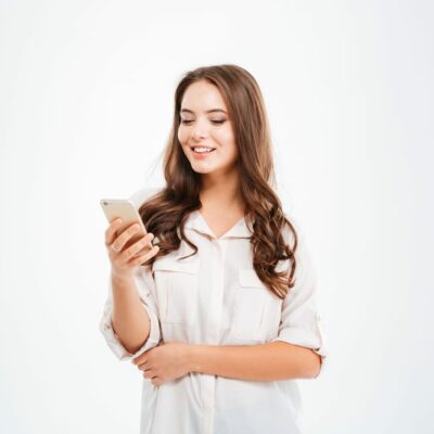 Woman holding a phone in a white background
