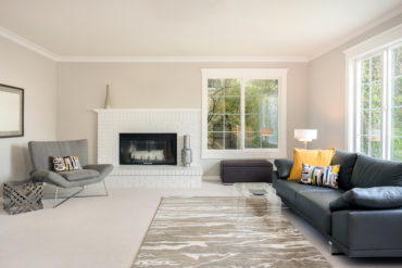 Modern spacious lounge or living room interior with designer furniture and fire place.